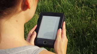 girl reading an e-book in nature