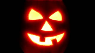 Halloween pumpkin jack-o-lantern candle lit, isolated on black
