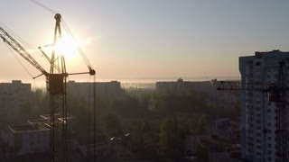 Industrial construction cranes and building silhouettes over sun at sunrise - aerial video shooting