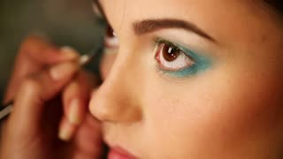 Makeup artist makes a bright eye makeup - stage make-up