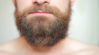 Man combing his mustache and beard