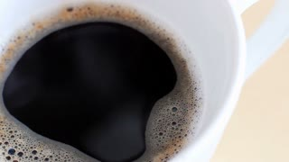 Pouring milk in the coffee close-up