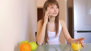 Pretty woman talking on the phone at breakfast at home