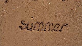 Sea wave on beach sand washes off an inscription summer