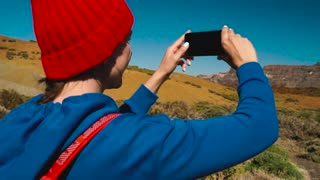 Active hiker woman hiking on Teide National Park and makes photo landscapes on the smartphone. Tenerife, Canary Islands, Spain