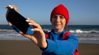 Active hiker woman walks on the beach and makes self photo on her smartphone. Caucasian young woman with backpack on Tenerife, Canary Islands, Spain. Slow motion
