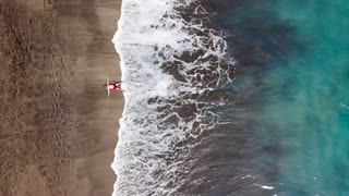 Aerial view of a man in red shorts lies on deserted black volcanic beach in a star pose. Aerial drone footage of sea waves reaching shore
