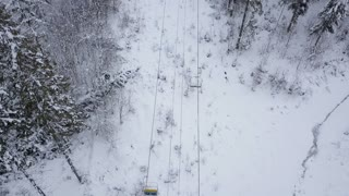Aerial view of ski resort - ski lift and snow-covered coniferous forest. Carpathians, Ukraine