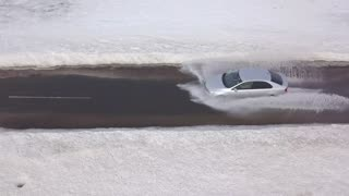 Aerial view on car car is driving through a puddle at high speed
