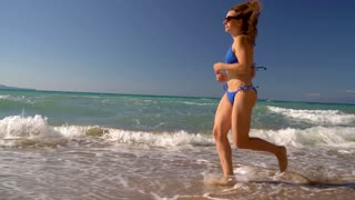 Beach bikini woman carefree running along the water on the beach. Picturesque sea coast of Corfu, Greece. Slow motion
