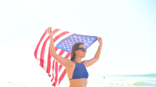 Beach bikini woman with US flag carefree walking along the water on the beach. Concept of Independence Day USA