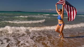 Beach bikini woman with US flag running along the water on the beach. Concept of Independence Day USA. Slow notion