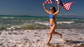 Beach bikini woman with US flag running along the water on the beach. Concept of Independence Day USA