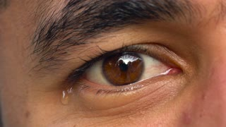 Beautiful eye of a man of Arab nationality close-up. The man is crying