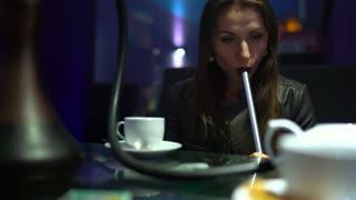 Beautiful young woman smoking a hookah and drinking tea