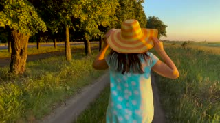 Beauty girl in yellow hat running outdoors in the countryside. Freedom concept