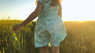 Beauty girl running in a yellow hat on green wheat field over sunset sky. Freedom concept. Wheat field in sunset. Slow motion
