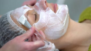Beauty specialist using brush to apply cosmetic mask on girl's face at the spa