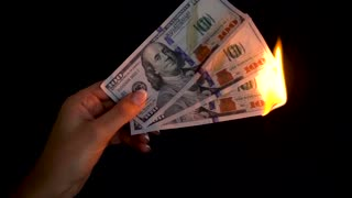 Burning dollars in a hand close-up on a black background. Slow motion