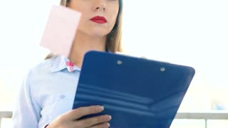 Businesswoman looking at sticky notes on glass board