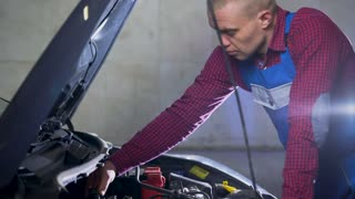 Car service, repair, maintenance and people concept - auto mechanic working at workshop
