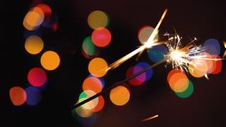 Christmas sparkler burning on a background of christmas tree with colorful bokeh and christmas lights