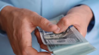 Close-up of man's hands counting hundred dollar bills