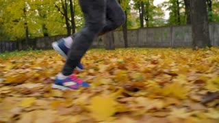 Close up of woman legs running through an autumn park at sunset. Slow motion