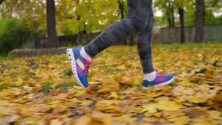 Close up of woman legs running through an autumn park at sunset