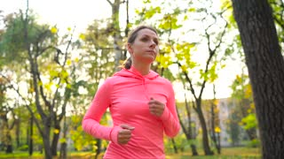 Close up of woman running through an autumn park at sunset. Slow motion