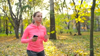 Close up of woman with headphones and smartphone running through an autumn park at sunset. Slow motion