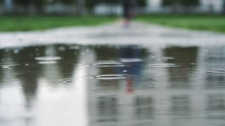 Close up shot in different speed of legs of a runner in sneakers. Female sports man jogging outdoors in a park, stepping into muddy puddle.
