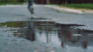 Close up slow motion shot of legs of a runner in sneakers. Female sports man jogging outdoors in a park, stepping into muddy puddle.