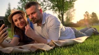 Couple in love lies on a plaid in the park and making self photo at sunset