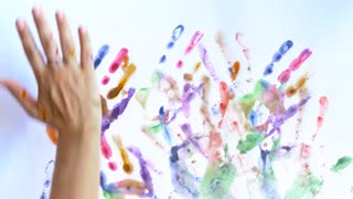Creative concept - man and woman make prints of their painted hands on a white background