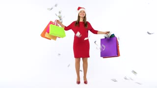 Dollar bills falling on Christmas shopping woman with multicolored shopping bags and crazy dancing on white background in studio. Let's go holiday shopping concept. Slow motion