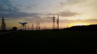 Drone flies over power lines at sunset