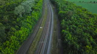 Empty straight double-way railways surrounded by green forest, aerial top view