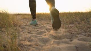 Female legs running along a sandy beach to the ocean