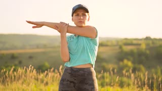 Fitness woman warms up and stretching outdoors before run. Slow motion