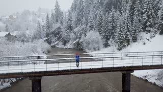 Flight over snowstorm in a snowy mountain coniferous forest and girl standing on a bridge across a mountain river near a mountain covered with coniferous forest in winter