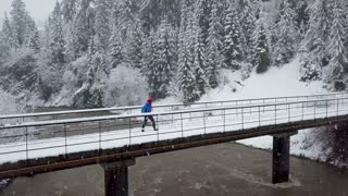Flight over snowstorm in a snowy mountain coniferous forest and girl walking along a bridge across a mountain river near a mountain covered with coniferous forest in winter