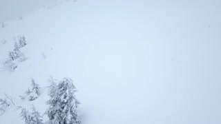 Flight over snowstorm in a snowy mountain, uncomfortable unfriendly winter weather.