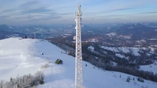 Flight over the mobile tower on top of Carpathian mountains covered with snow. Clear frosty weather