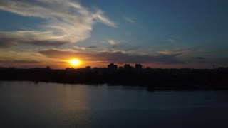 Flying over the trees and lake in the city at dawn - aerial videotaping