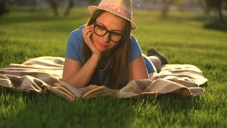 Girl in glasses reading book lying down on a blanket in the park at sunset