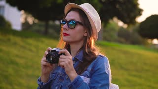 Girl is walking around the city and taking photos of nature and sights on a film camera