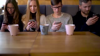 Group of people use mobile phones in a cafe instead of communicating with each other