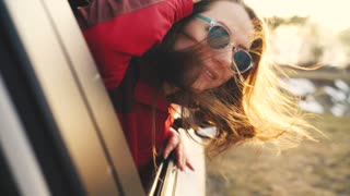 Happy young woman sitting in car passenger seat and looking out window on sunny day