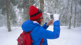 Lonely tourist girl walking on a winter snow-covered coniferous forest in the mountains and takes a photo of nature on a smartphone. Frosty weather